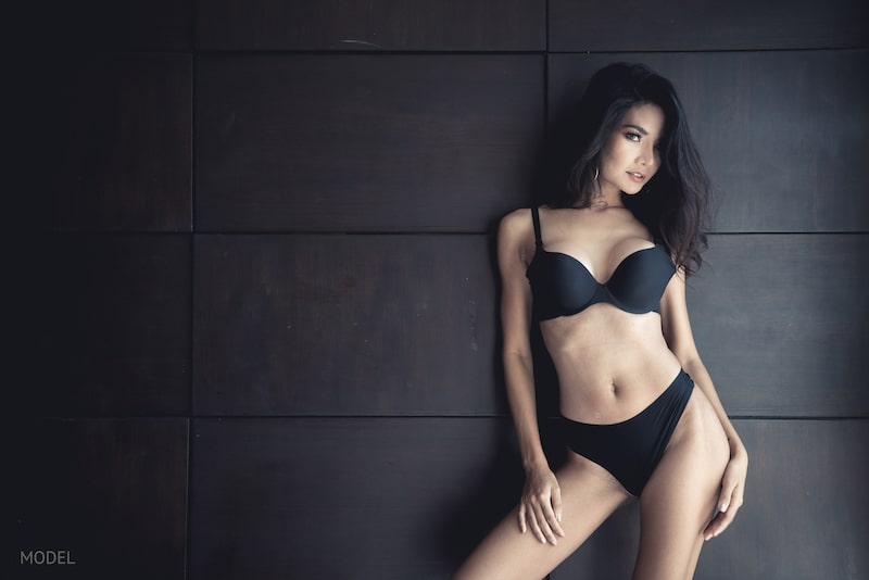 Asian woman in bra and underwear against a slate wall.