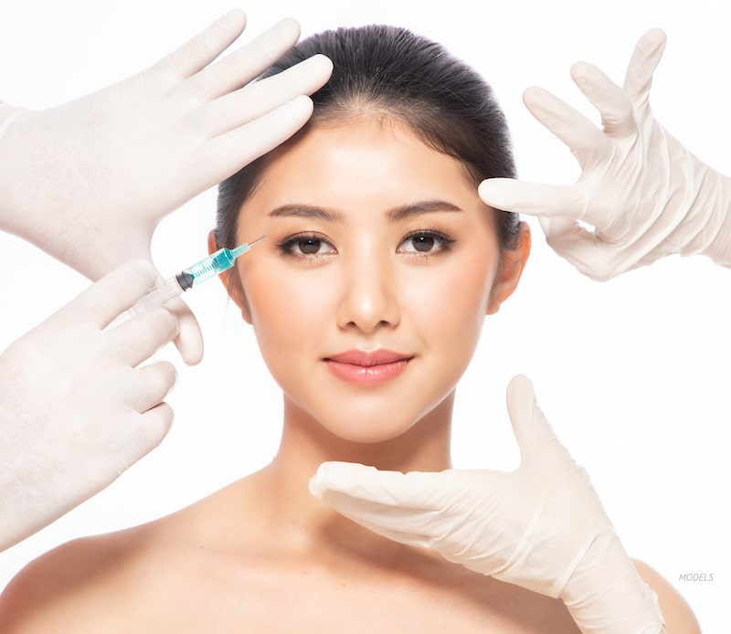 Young Asian women getting an injectable treatment at the corner of her eye.